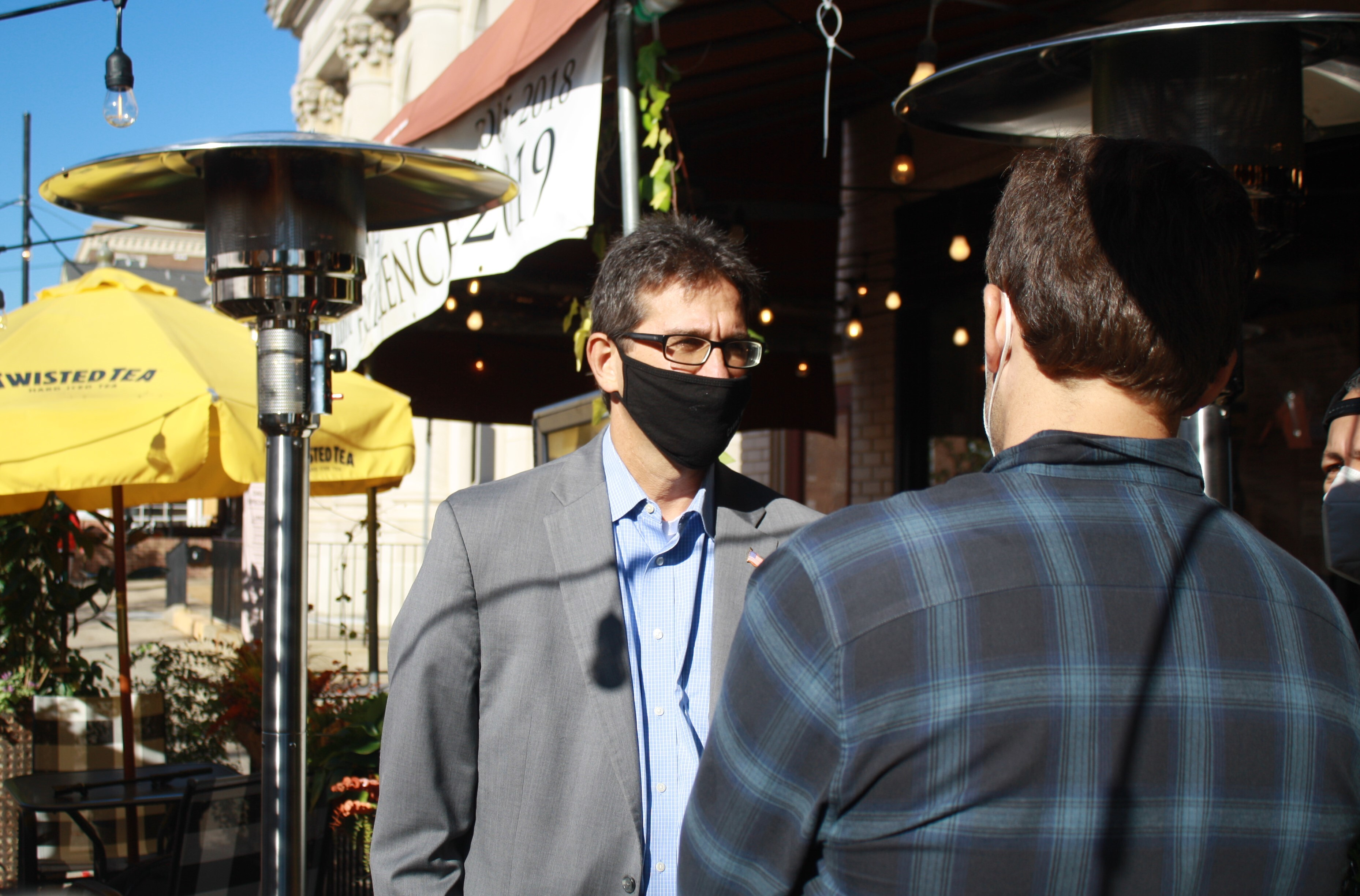 NCCo Executive Matt Meyer talks with Caffé Gelato owner Ryan German under heat lamps outside German's restaurant in downtown Newark