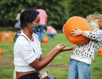 A woman and child at a pumpkin patch wearing masks