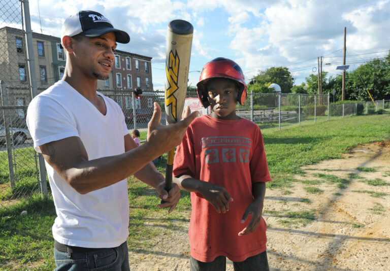 Bryan Morton coaches a child in Camden in 2011, at about the time he founded the North Camden Little League. (April Saul for WHYY)