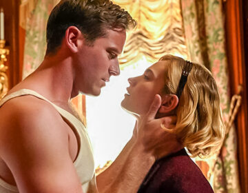 Armie Hammer and Lily James in an embrace in the movie Rebecca