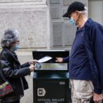 Alice and Len Sayles return their ballots in the drop box outside City Hall