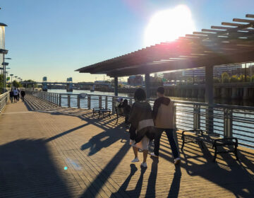 People walk along the Schuylkill Banks Boardwalk
