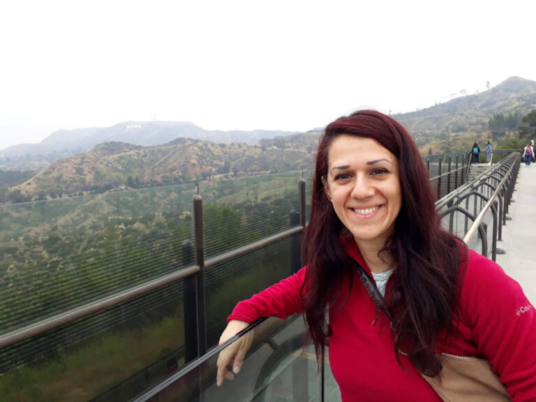 Woman with long reddish hair and a red shirt smiles by a scenic overlook