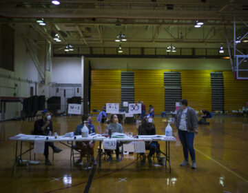 First-time election workers, seated, from left to right,  Chris DiStasi, Kaitlin Irvine, Alicia Dlugos and Katie Phillips, end their day at South Philadelphia High School, a polling site on South Broad Street. (Alan Chin for WHYY)