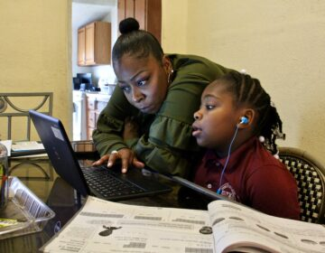 Yolanda Biggers helps her daughter, Zyiah Satterwhite, 7, find her assignment.  After the coronavirus pandemic hit, Biggers gave up her shifts as a part-time nurse to focus all of her attention on Zyiah and her two older sisters as they adapted to virtual schooling. (Emma Lee/WHYY)
