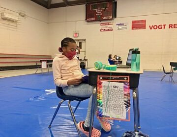 Faith Allen, 10, reads at her desk in Vogt access center gymnasium. (Emily Rizzo/WHYY)