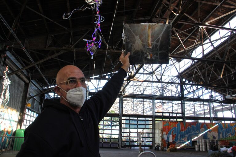 John Schlesinger holds a still life painting, broken and repaired, up to the light at the Cherry Street Pier. The work produces the desired effect when lit from behind. (Emma Lee/WHYY)