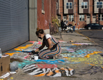 "Natalie Flor Negron creates a mural titled ""Ancient Roots"" for the Philadelphia Chalk Festival outside the Philadelphia Brewing Company in Kensington. (Kimberly Paynter/WHYY)"