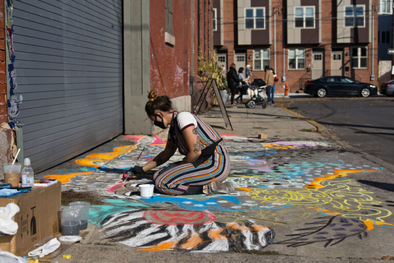 """Natalie Flor Negron creates a mural titled """"Ancient Roots"""" for the Philadelphia Chalk Festival outside the Philadelphia Brewing Company in Kensington. (Kimberly Paynter/WHYY)"""