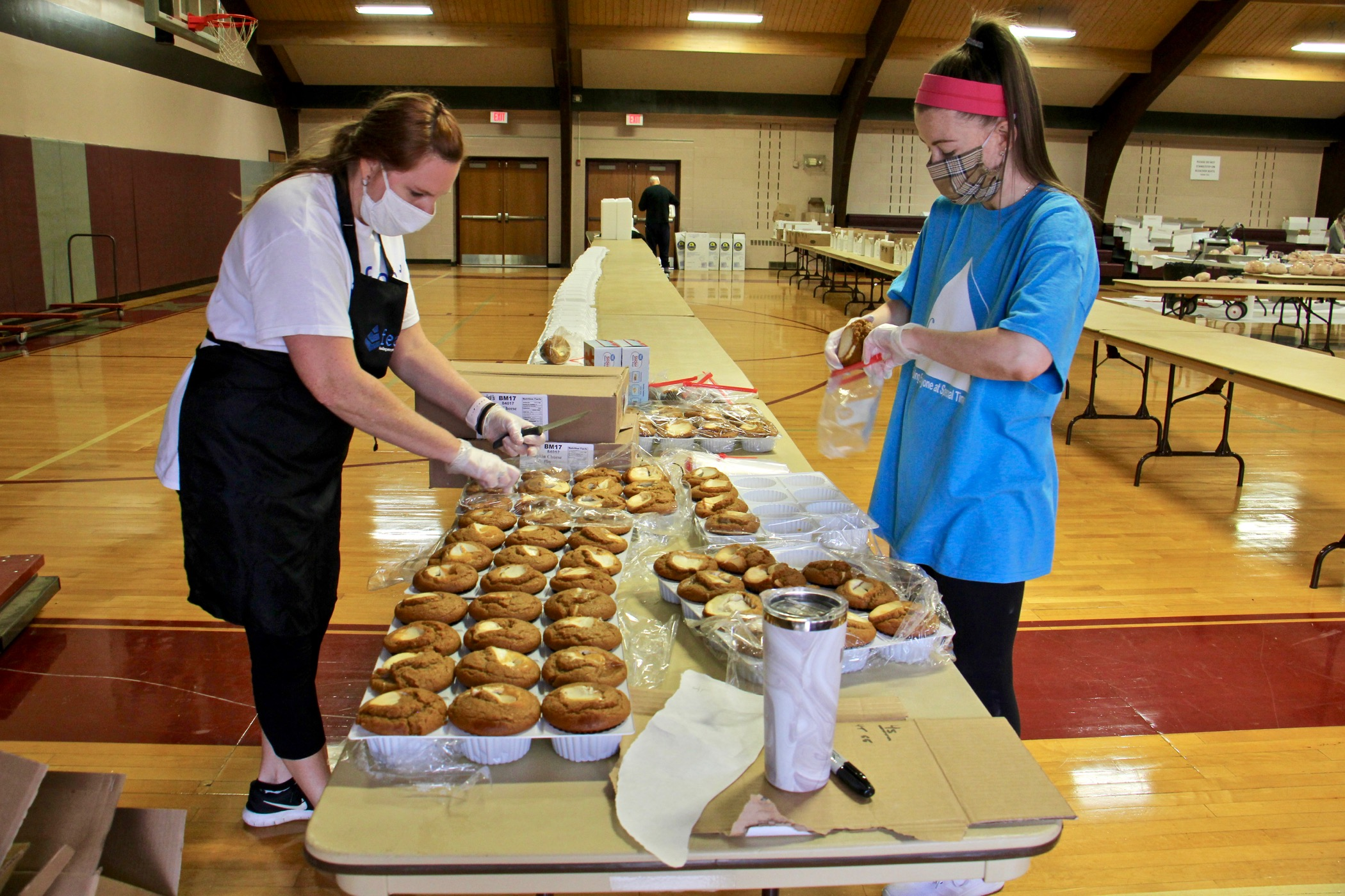 Colleen Fuchs (left) and Natalie Capobianco put together Thanksgliving meals at St. Robert Bellarmine Church