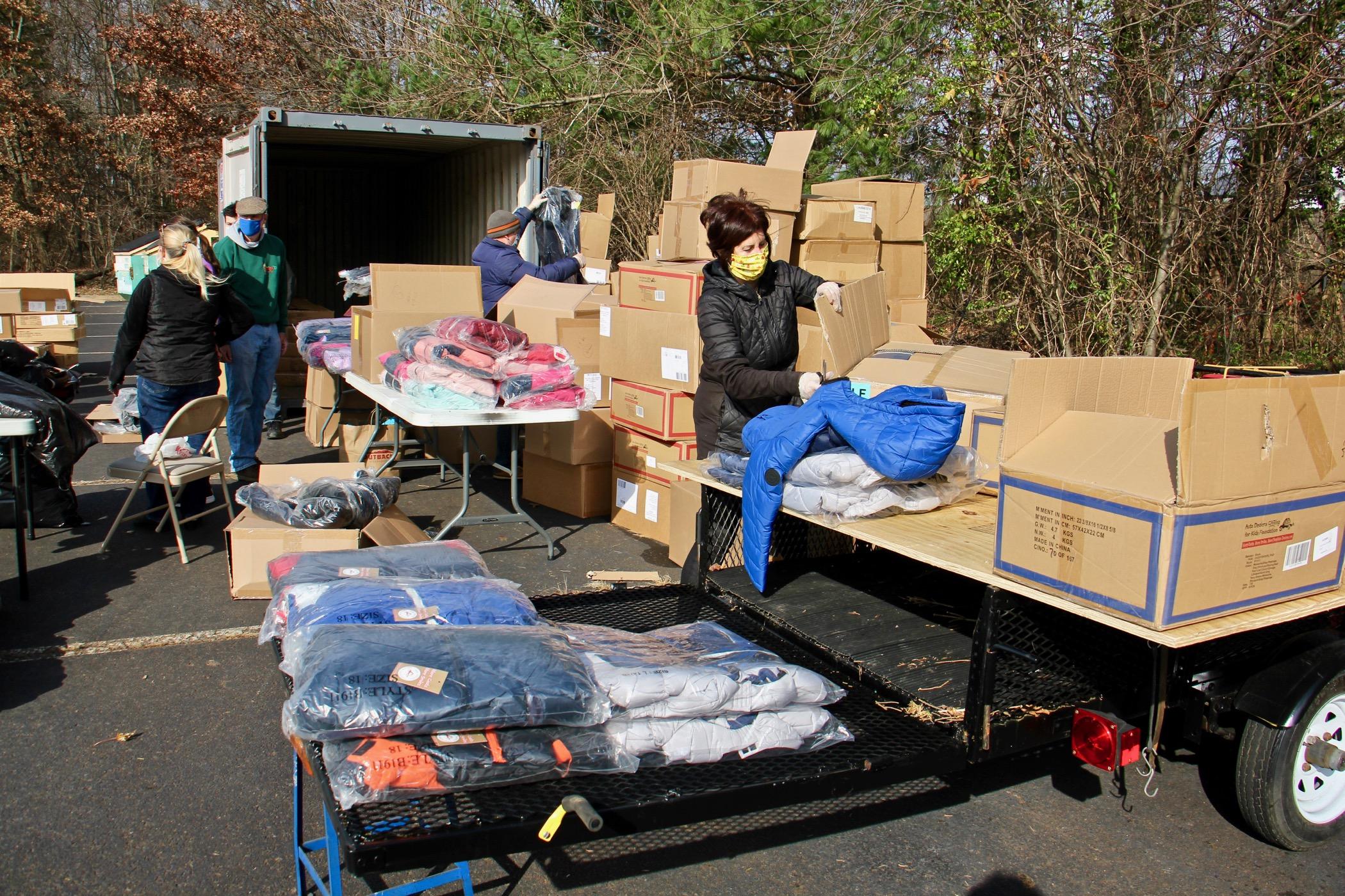 Volunteers unpack winter coats in the parking lot at St. Robert Bellarmine Church