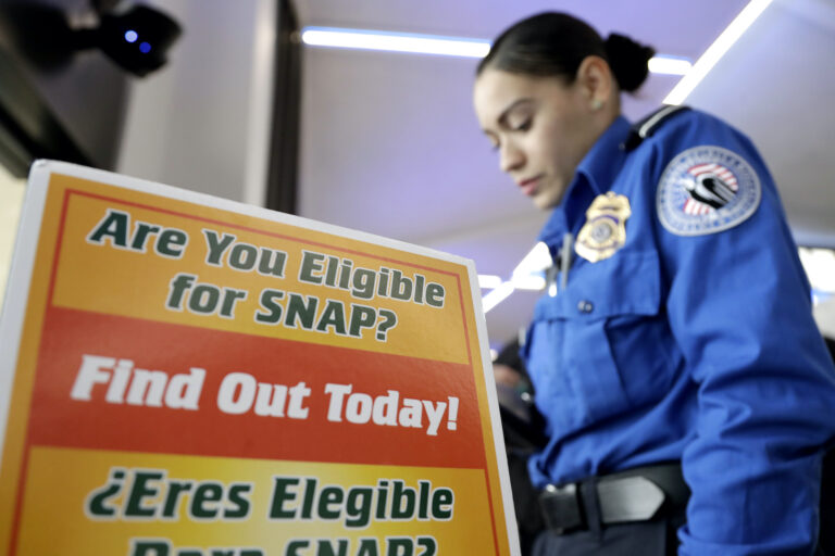 A Transportation Security Administration employee stands at a booth to learn about a food stamp program at a food drive at Newark Liberty International Airport to help government employees who are working without pay during the partial government shutdown, Wednesday, Jan. 23, 2019, in Newark, N.J. (AP Photo/Julio Cortez)