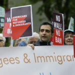 FILE - In this May 15, 2017, file photo, protesters hold signs during a demonstration against President Donald Trump's revised travel ban, outside a federal courthouse in Seattle.  Refugee advocates, including faith-based groups that President Donald Trump is courting in his re-election bid, called on Congress Thursday, Oct. 1, 2020, to halt his administration's plans to slash the limit on refugees allowed into the U.S. to a record low, saying it goes against America's values.    (AP Photo/Ted S. Warren, File)