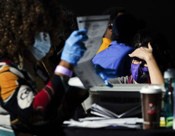 A election supervisor answer questions for the election workers as they count ballots at State Farm Arena on Thursday, Nov. 5, 2020, in Atlanta. (AP Photo/Brynn Anderson)