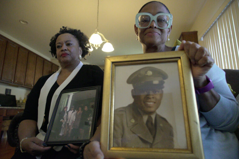 Sisters Barbara Leak-Watkins, right, and Alberta Lynn Fantroy pose with photos of their late father, Alex Leak Jr., at Watkins' home in Greensboro, N.C., on Wednesday, Nov. 4, 2020. The Army veteran died in July after collapsing from dehydration at his assisted living facility, and the family believe pandemic-related neglect is to blame. (AP Photo/Allen G. Breed)