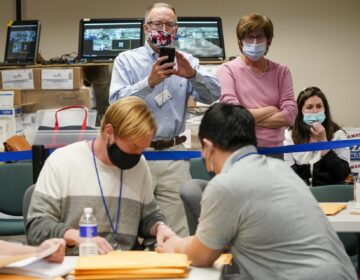 Republican canvas observer Ed White, center, and Democratic canvas observer Janne Kelhart, watch as Lehigh County workers count ballots as vote counting in the general election continues, Friday, Nov. 6, 2020, in Allentown, Pa. (Mary Altaffer/AP Photo)