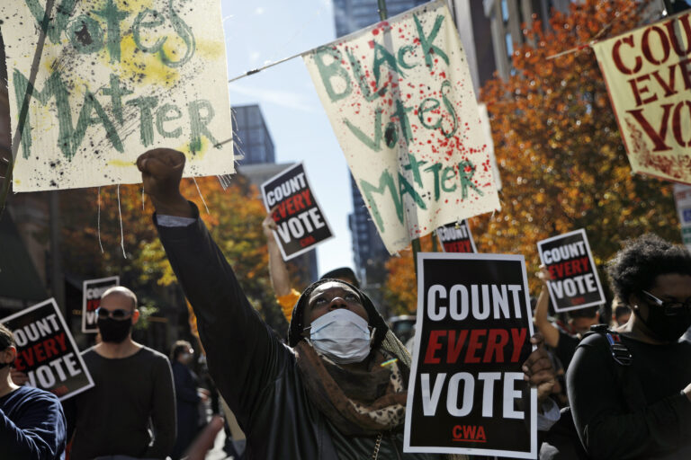 Zhanon Morales, 30, of Philadelphia, raises her fist as demonstrators call for all votes be counted during a rally outside the Pennsylvania Convention Center, Thursday, Nov. 5, 2020, in Philadelphia. (AP Photo/Rebecca Blackwell)