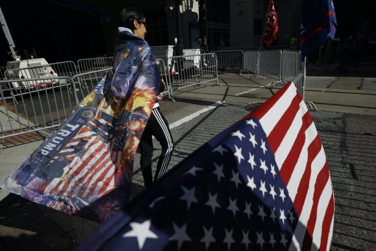 A woman wears a Trump flag as a cape as supporters of President Donald Trump protest outside the Pennsylvania Convention Center, where vote counting continues, in Philadelphia, Monday, Nov. 9, 2020, two days after the 2020 election was called for Democrat Joe Biden. (AP Photo/Rebecca Blackwell)