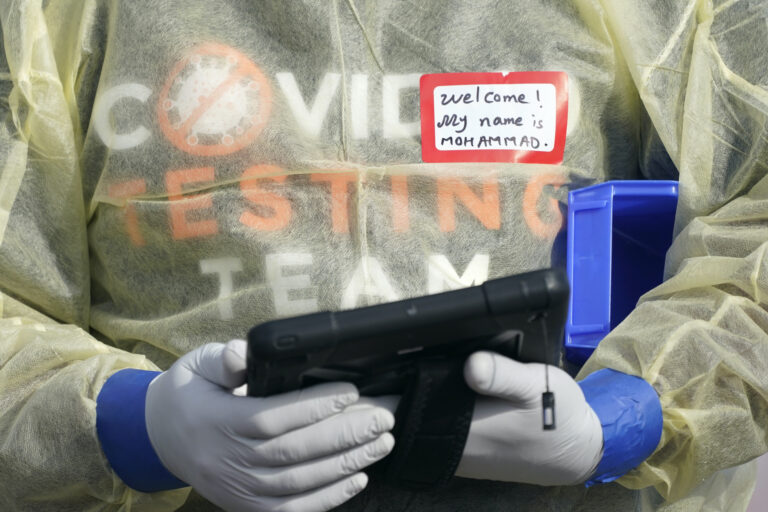 A worker wearing gloves, and other PPE holds a tablet computer as he waits to check people in, Wednesday, Oct. 28, 2020, at a King County coronavirus testing site in Auburn, Wash., south of Seattle. (AP Photo/Ted S. Warren)