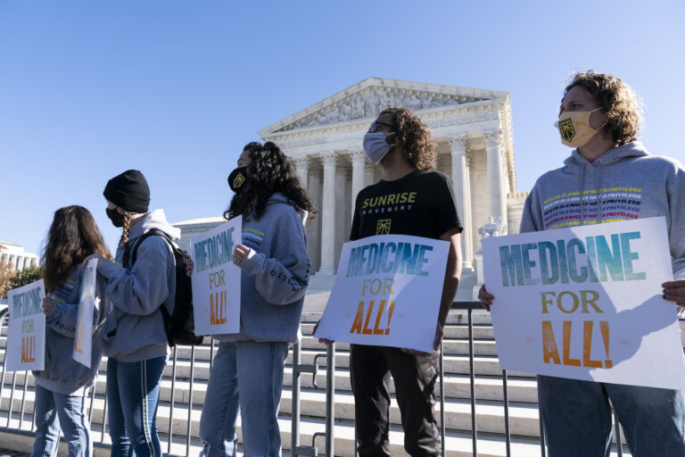 Demonstrators hold signs in front of the U.S. Supreme Court as arguments are heard about the Affordable Care Act Tuesday, Nov. 10, 2020, in Washington. (AP Photo/Alex Brandon)