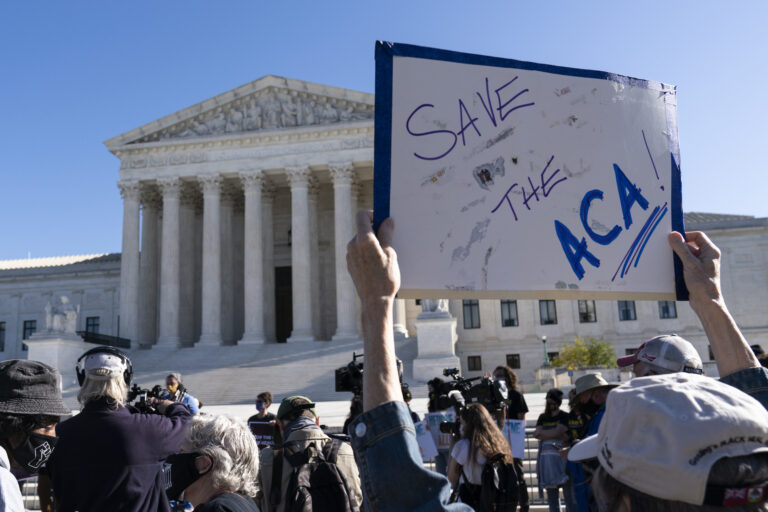 A demonstrator holds a sign in front of the U.S. Supreme Court as arguments are heard about the Affordable Care Act, Tuesday, Nov. 10, 2020, in Washington. (AP Photo/Alex Brandon)
