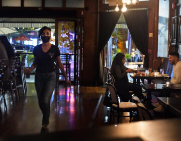 Patrons enjoy food and drink at The Brass Rail in Hoboken, N.J., Wednesday, Nov. 11, 2020. The number of confirmed COVID-19 cases surged by almost 4,000 new cases, Gov. Phil Murphy said Tuesday, the highest increase in nearly seven months. The so-called second wave led Murphy this week to announce that indoor dining at bars and restaurants must halt from 10 p.m. to 5 a.m. beginning on Thursday. (AP Photo/Seth Wenig)