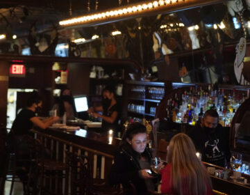 Patrons enjoy food and drink at The Brass Rail in Hoboken, N.J., Wednesday, Nov. 11, 2020. (AP Photo/Seth Wenig)