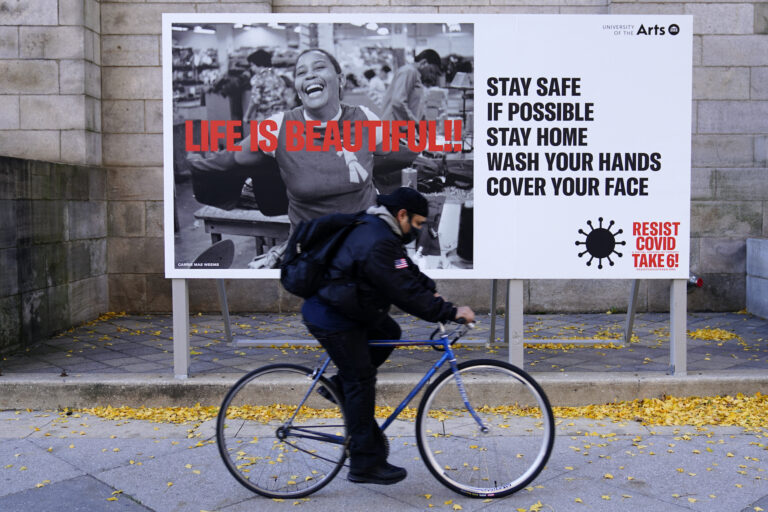 A man wearing a face mask bicycles along Broad Street, Wednesday, Nov. 18, 2020, in Philadelphia. (AP Photo/Matt Slocum)