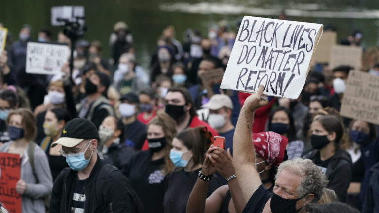 In this Sept. 29, 2020, file photo, a man holds a sign during a protest, in Cleveland. (AP Photo/Tony Dejak)