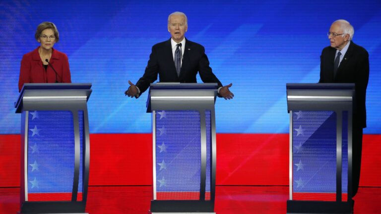 In this Feb. 7, 2020, file photo Democratic presidential candidate former Vice President Joe Biden, center, speaks as Sen. Elizabeth Warren, D-Mass., left, and Sen. Bernie Sanders, I-Vt., listen during a Democratic presidential primary debate hosted by ABC News, Apple News, and WMUR-TV at Saint Anselm College in Manchester, N.H. (AP Photo/Elise Amendola)