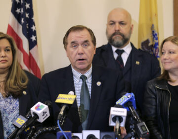 In this March 25, 2019 file photo, Assembly Speaker Craig Coughlin, center, speaks to reporters in Trenton, N.J. (AP Photo/Seth Wenig)