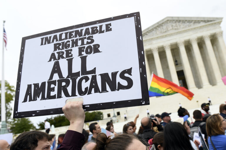 In this Oct. 8, 2019, file photo, protesters gather outside the Supreme Court in Washington where the Supreme Court is hearing arguments in the first case of LGBT rights since the retirement of Supreme Court Justice Anthony Kennedy.  (AP Photo/Susan Walsh)