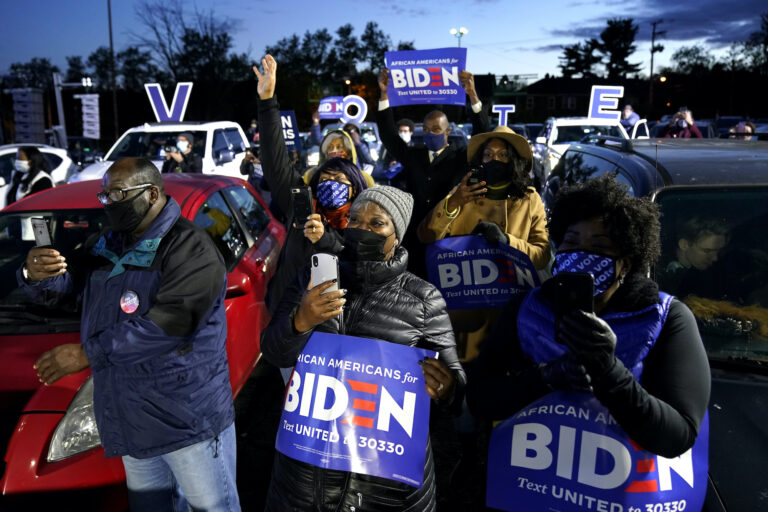 Supporters listen as Democratic presidential candidate former Vice President Joe Biden speaks at a drive-in campaign rally