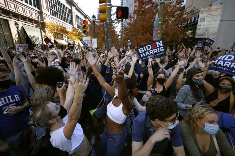 People dance as they celebrate outside the Pennsylvania Convention Center