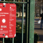 A sign at the entrance to a park warns pedestrians about increased risk for the coronavirus in the Ironbound section of Newark