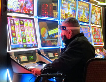A man wears a face shield while playing a slot machine at the Golden Nugget casino