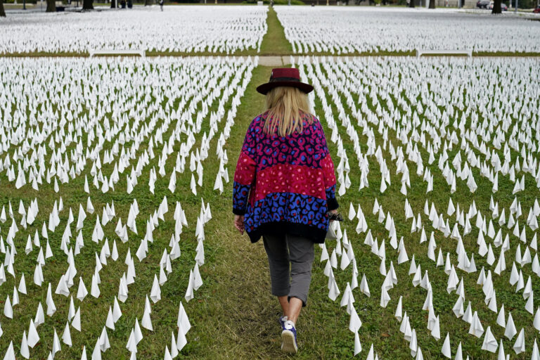 Artist Suzanne Brennan Firstenberg walks among thousands of white flags planted in remembrance of Americans who have died of COVID-19