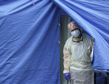 A medical worker operates a testing tent at a COVID-19 mobile testing site