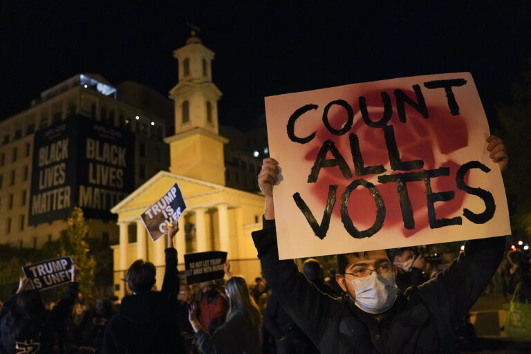 A demonstrator holds up a sign while waiting for election results