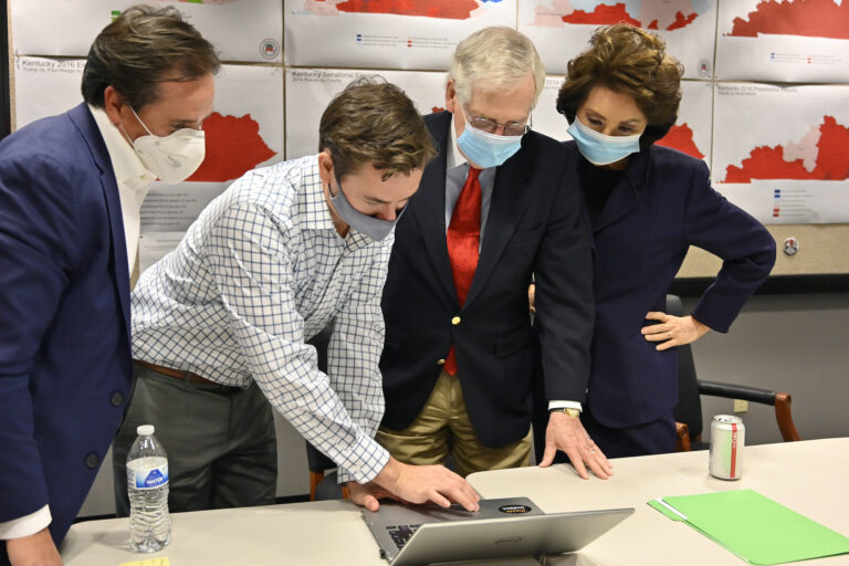 Republican Senate candidate Sen. Mitch McConnell, center, and his wife, Secretary of Transportation Elaine Chao, right, look on as aides show him the election results