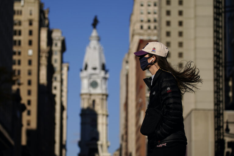 A woman wearing a face mask crosses Broad Street
