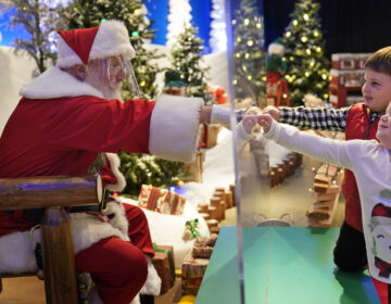 Julianna, 3, and Dylan, 5, Lasczak visit with Santa through a transparent barrier