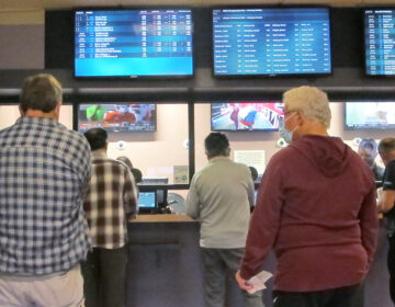 Customers line up to make sports bets at Freehold Raceway in Freehold