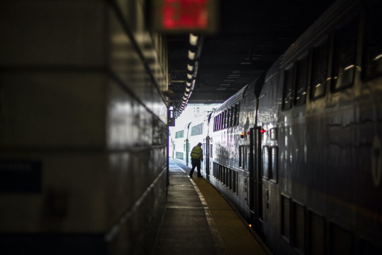 A train employee boards the commuter rail heading to Boston after waiting for passengers.