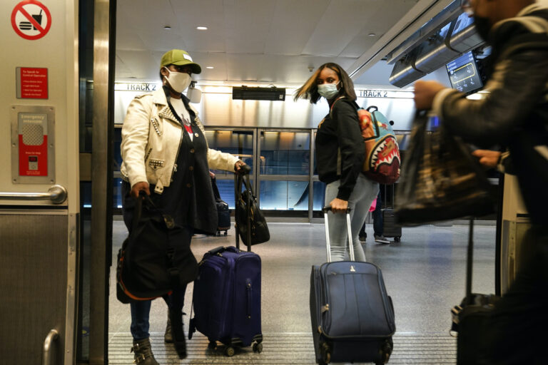 Travelers leave the AirTrain at JKF International Airport