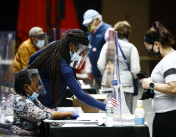 Election workers, left, check in voters before they cast their ballots in the Pennsylvania primary in Philadelphia