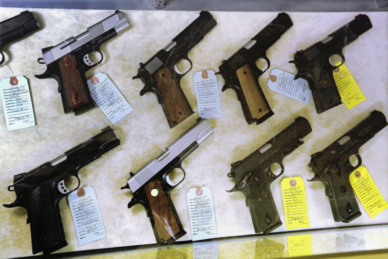 In this July 10, 2013 file photo, semi-automatic handguns are seen displayed for purchase at an arms supply store in Springfield, Ill. (AP Photo/Seth Perlman)