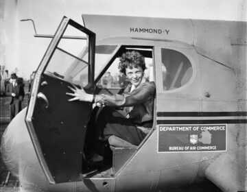 Amelia Earhart sitting in an airplane