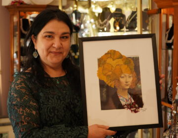 Ylvia Asal holding up a piece of her artwork in her Anatolia Art & Craft Studio. (Kenny Cooper/WHYY)