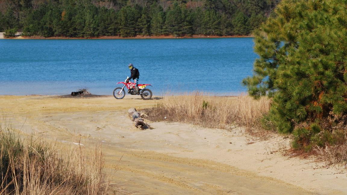 A dirt-bike rider cruises the edge of Cedar Lake.
